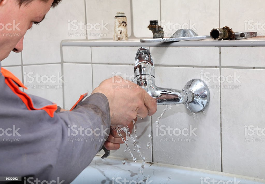 Man fixing the bathroom faucet with white tiles stock photo