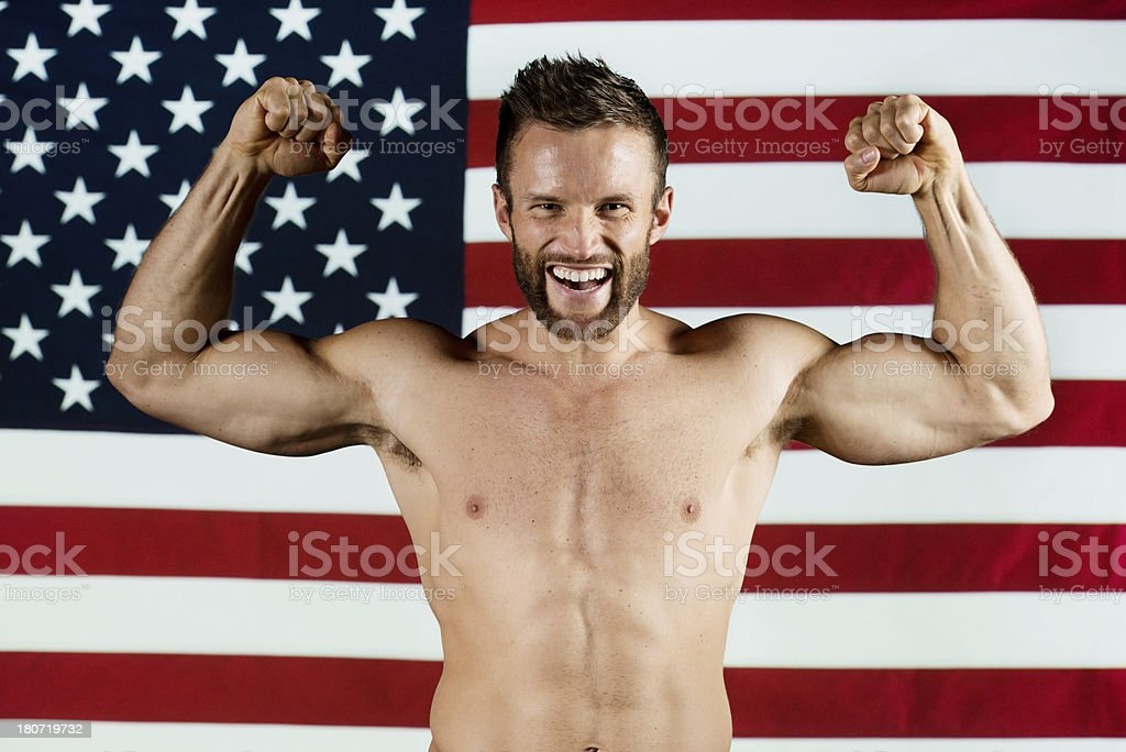 Man flexing his biceps in front of American flag royalty-free stock photo