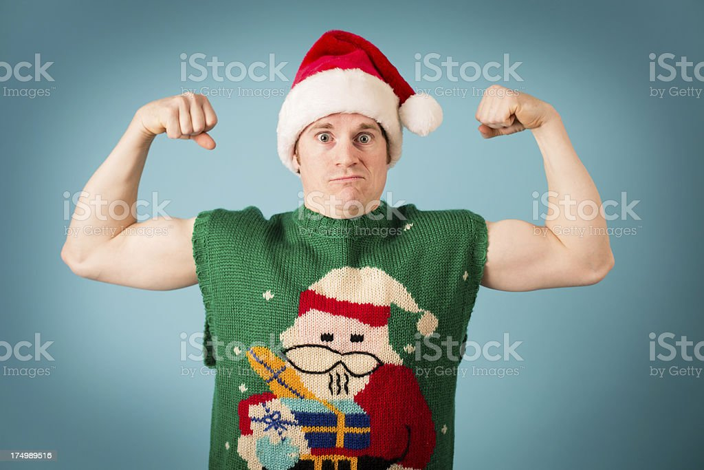 Man Flexing Muscles, Wearing Santa Hat and Ugly Vest royalty-free stock photo