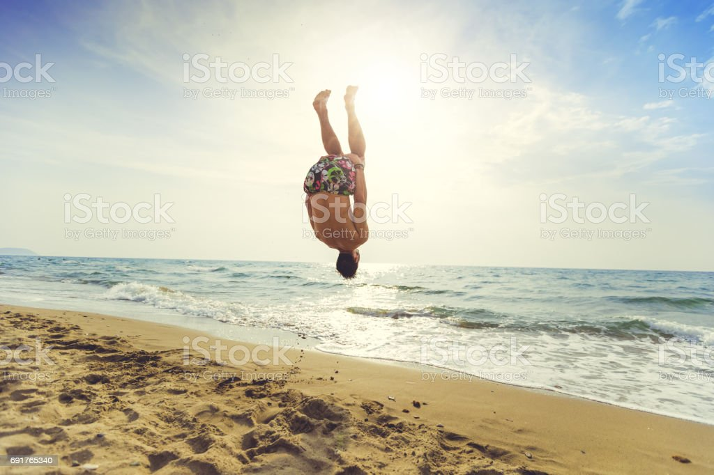 4d97eacf1 Man flips and spins a sommersault on the beach royalty-free stock photo