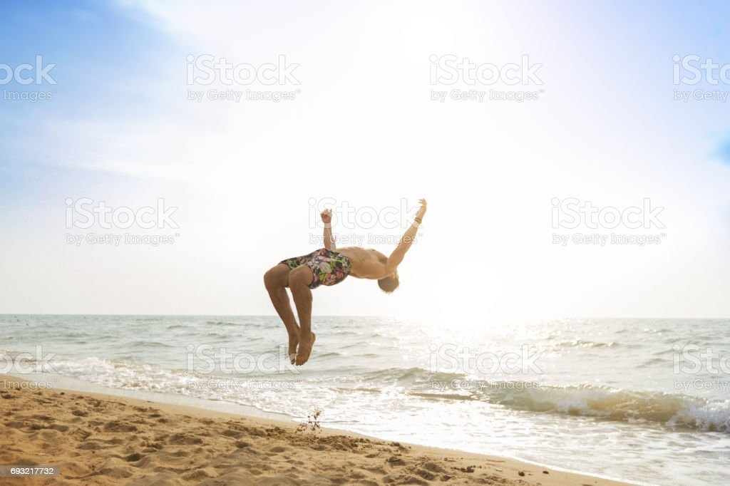 Man flips and spins a sommersault on the beach stock photo