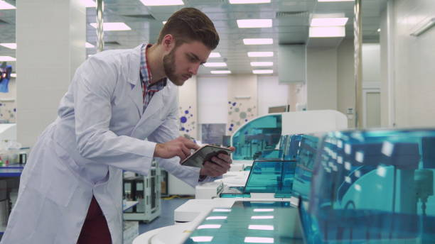 Man flips on the tablet near laboratory machine Attractive caucasian man in white coat flipping on the tablet near laboratory machine. Young male scientist coming close to the lab equipment. Handsome bearded guy looking at the centrifugal machine biochemist stock pictures, royalty-free photos & images