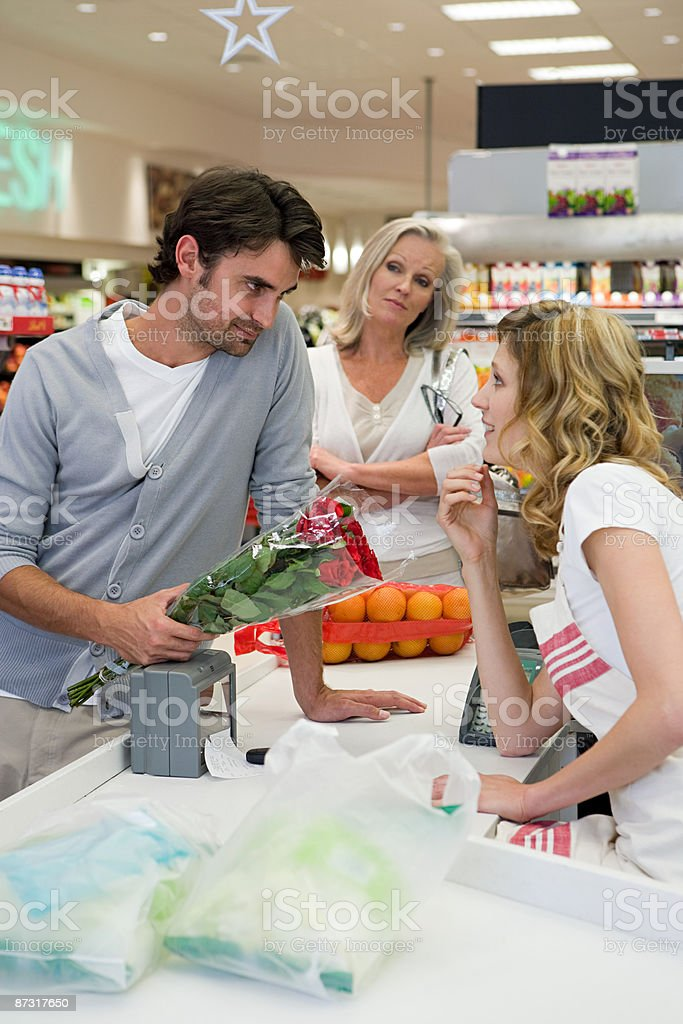 Man flirting with sales assistant stock photo