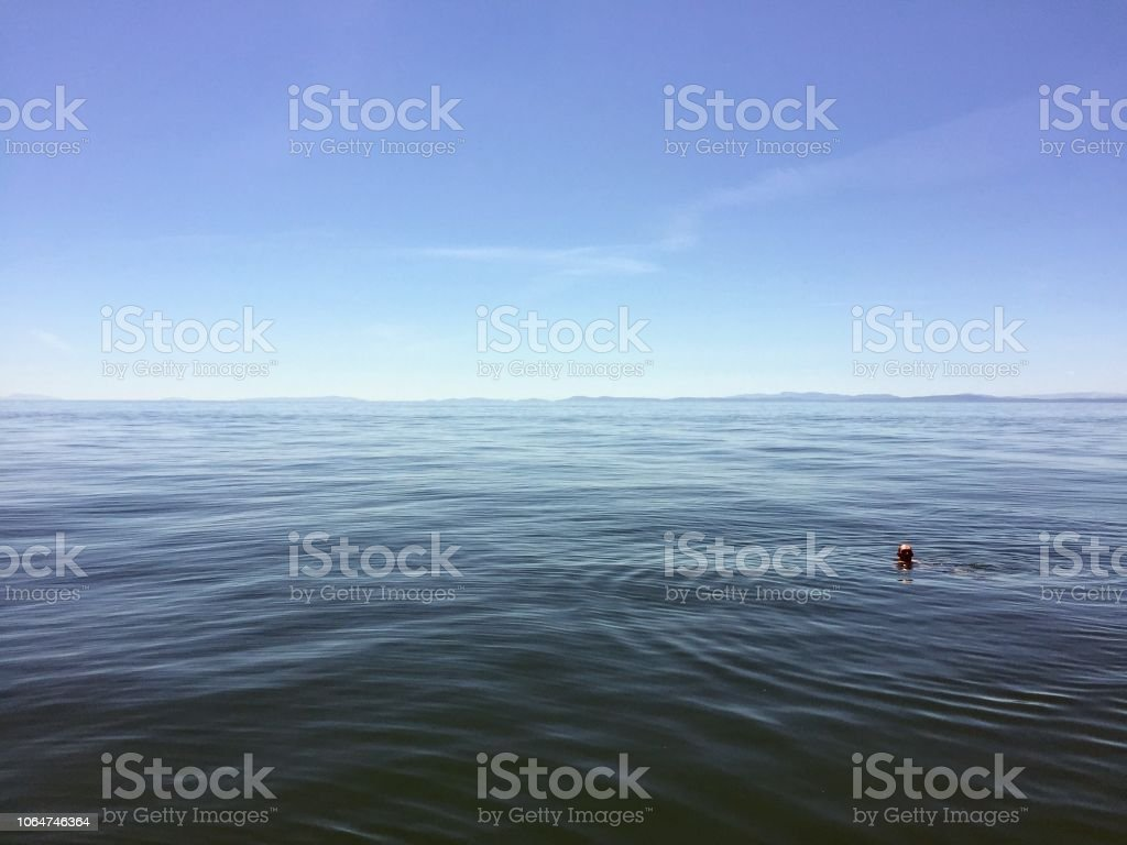 A man floating in the open ocean with no land in sight.