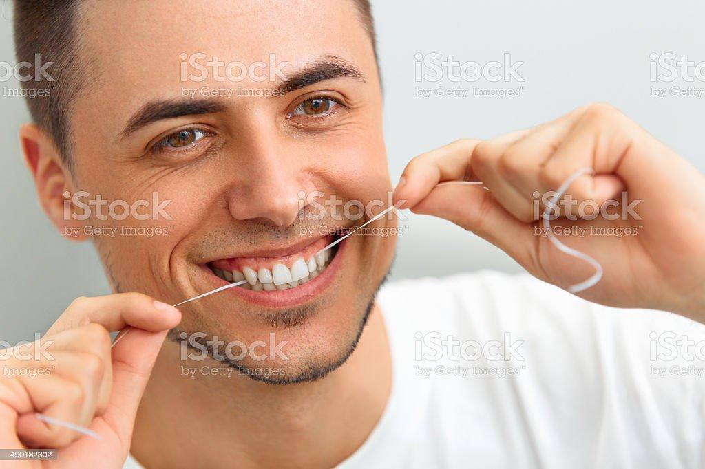 Mann seine Zähne flossing. Reinigung der Zähne mit Zahnseide – Foto
