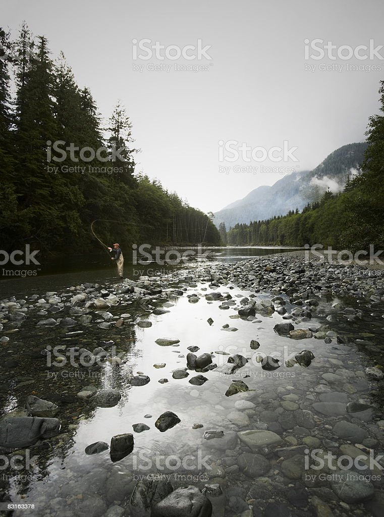 Man fly fishing in river  royaltyfri bildbanksbilder