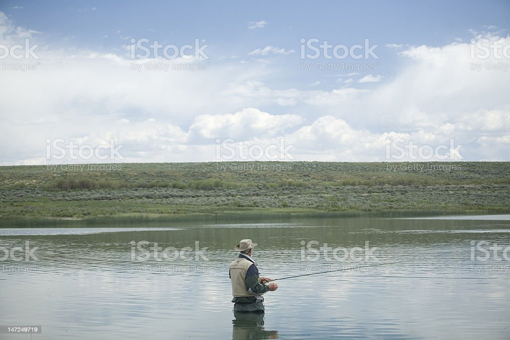 Man fly fishing in small lake royalty-free stock photo