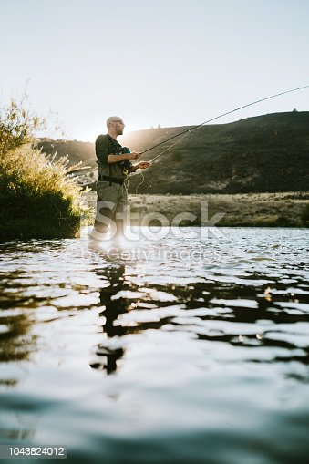 A man fly fishing on the Deschutes river in Warm Springs, Oregon, fishing for trout.