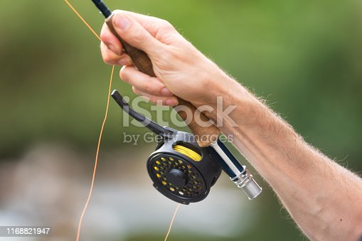 1094918172 istock photo Man fly fishing with reel and rod. Sport fly fisher man close up on reel. 1168821947