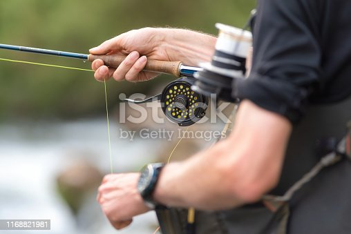 914030378 istock photo Man fly fishing with reel and rod. Sport fly fisher man close up on reel. 1168821981