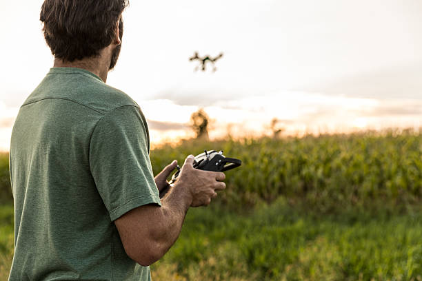man flying a drone at sunset - drones stock photos and pictures