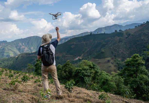 man fliegt eine drohne auf dem lande - flugdrohne stock-fotos und bilder