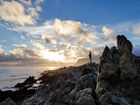 A man stands on the rocks and operates a drone from a remote controller in his hand late in the afternoon as the sun sets