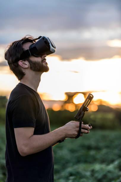 仮想現実ゴーグル ヘッドセットとドローンを飛ぶ男 - リモート ストックフォトと画像