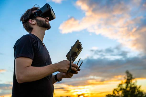 man fliegt eine drohne mit virtual-reality-brille-kopfhörer - flugdrohne stock-fotos und bilder