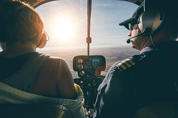 man flying a helicopter with his copilot - pilot stock photos and pictures