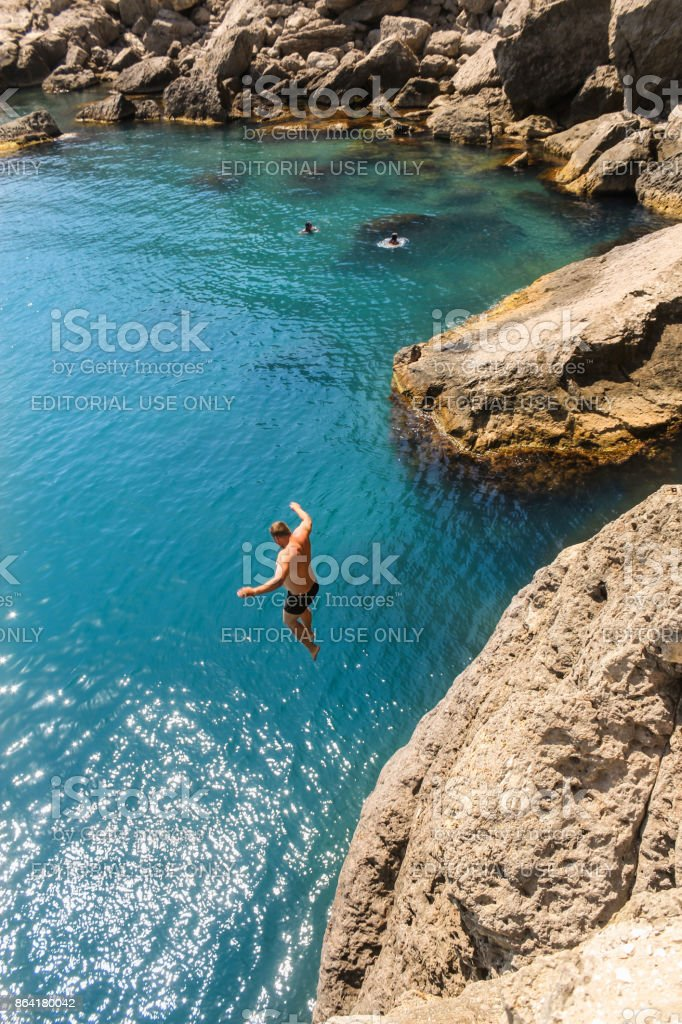 A man flying from a rock into the water. royalty-free stock photo