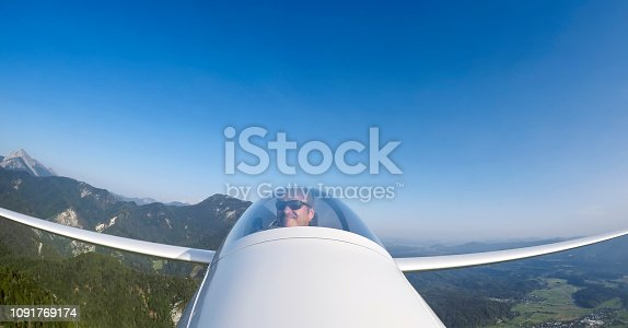 Mature man flying glider airplane against blue sky.
