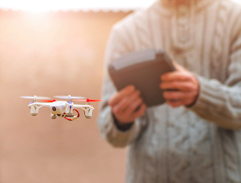 Paris, France - January 3, 2015: Hubsan FPV X4, small quadricopter drone flying in selective focus with unrecognizable man in background. It's the world's smallest FPV (first person view) quadcopter. The toy has a front camera to see the captured image directly on the remote control. 2.4GHz RC series, 480p camera and 4.3 inch LCD. Hubsan is a leader in flying object model.