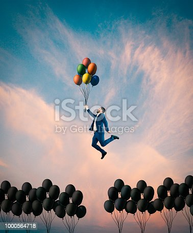 istock Man flying with colorful balloons. 1000564718