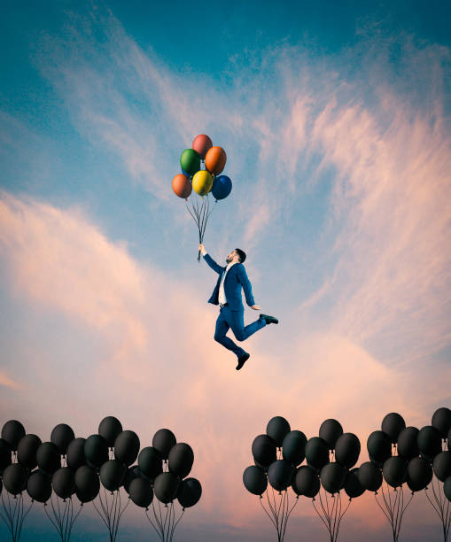 man flying with colorful balloons. - passione foto e immagini stock