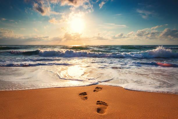 Mann tritt am Strand in Richtung Meer, orange Sonnenaufgang erschossen – Foto