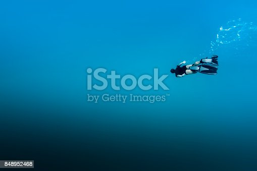A DSLR Canon underwater photo of a 41-year-old Brazilian man free diving into clear turquoise water at Baía do Sancho in Fernando de Noronha, Pernambuco, Brazil.