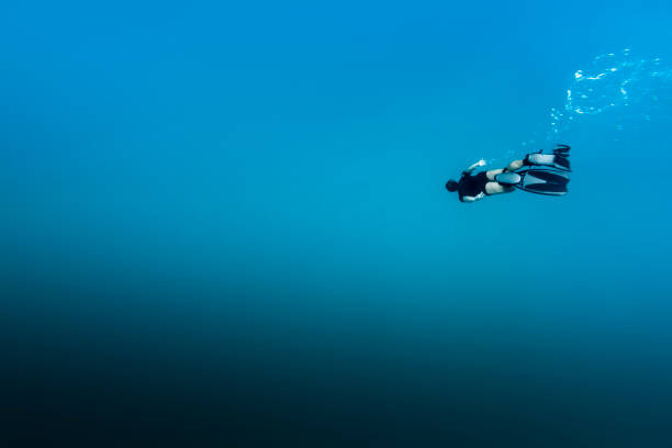 Man free diving in Fernando de Noronha A DSLR Canon underwater photo of a 41-year-old Brazilian man free diving into clear turquoise water at Baía do Sancho in Fernando de Noronha, Pernambuco, Brazil. deep stock pictures, royalty-free photos & images