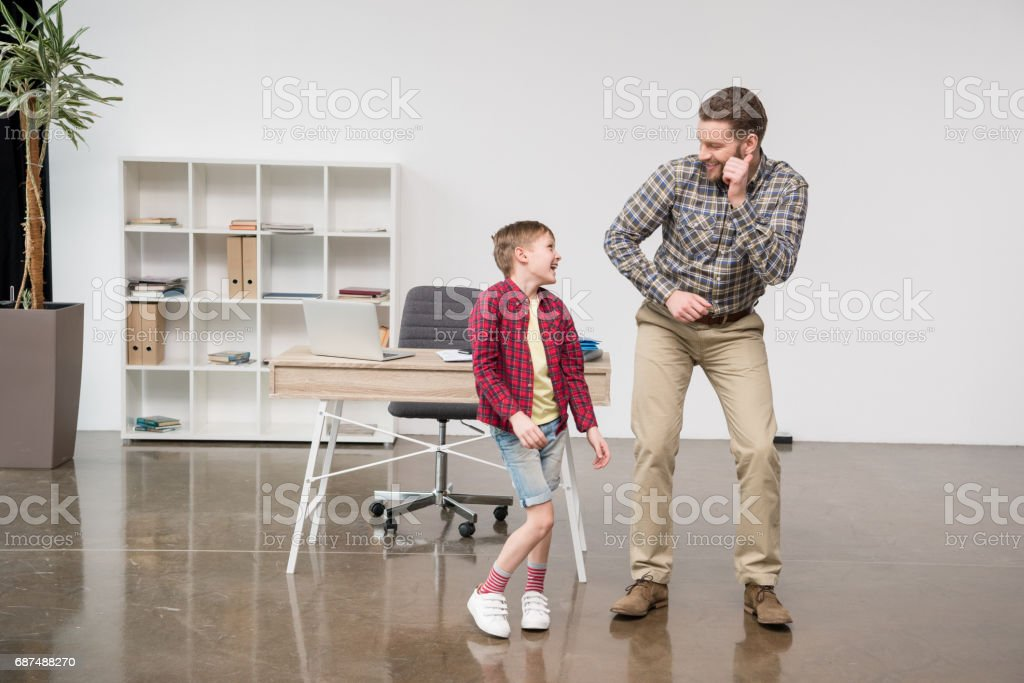 Man freelancer having fun with son at home office stock photo