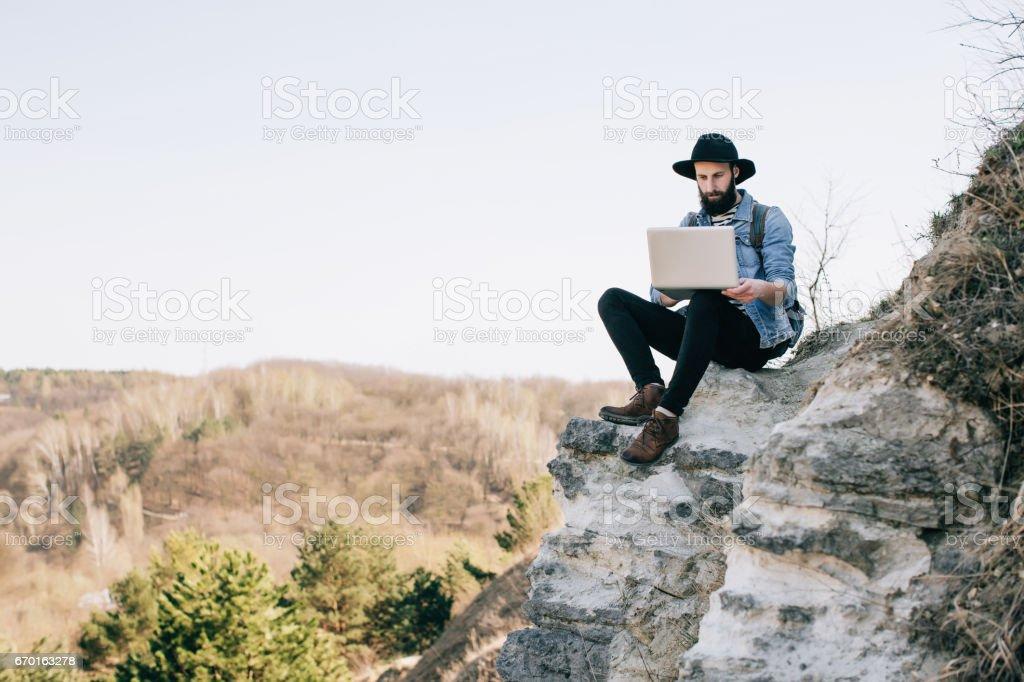 freelancer de homem trabalhando com um laptop nas montanhas. conceito de trabalho - foto de acervo