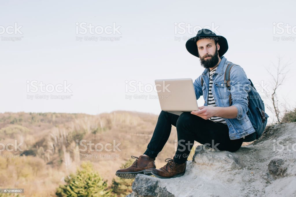 man freelancer working with a laptop in the mountains. work concept - foto de acervo