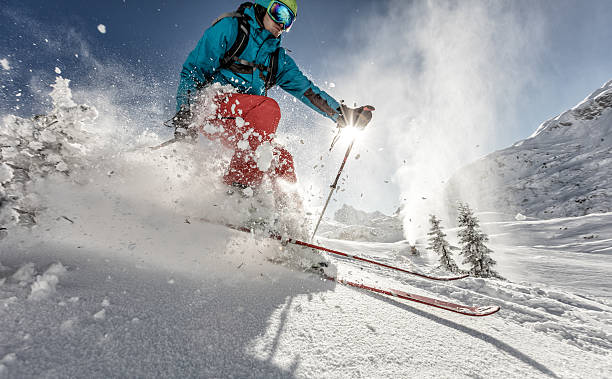 Man freerideer running downhill Man freeride skier running downhill on sunny Alps slope. ski stock pictures, royalty-free photos & images