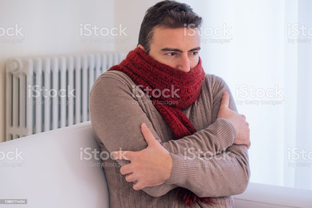 Man freezing and shivering at home because of winter cold stock photo