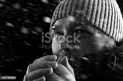 Freezing cold man standing in a snow storm blizzard trying to keep warm. Wearing a beanie hat and winter coat with frost and ice on his beard and eyebrows. Black and white. Looking to the left.