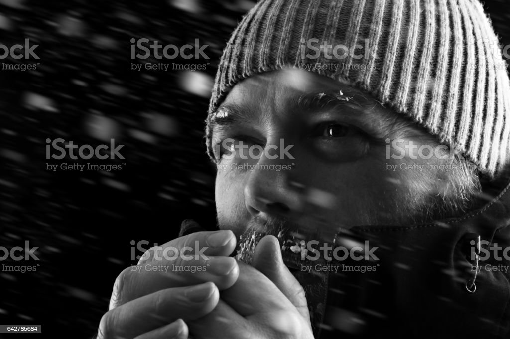 Man freezing in snow storm BW stock photo