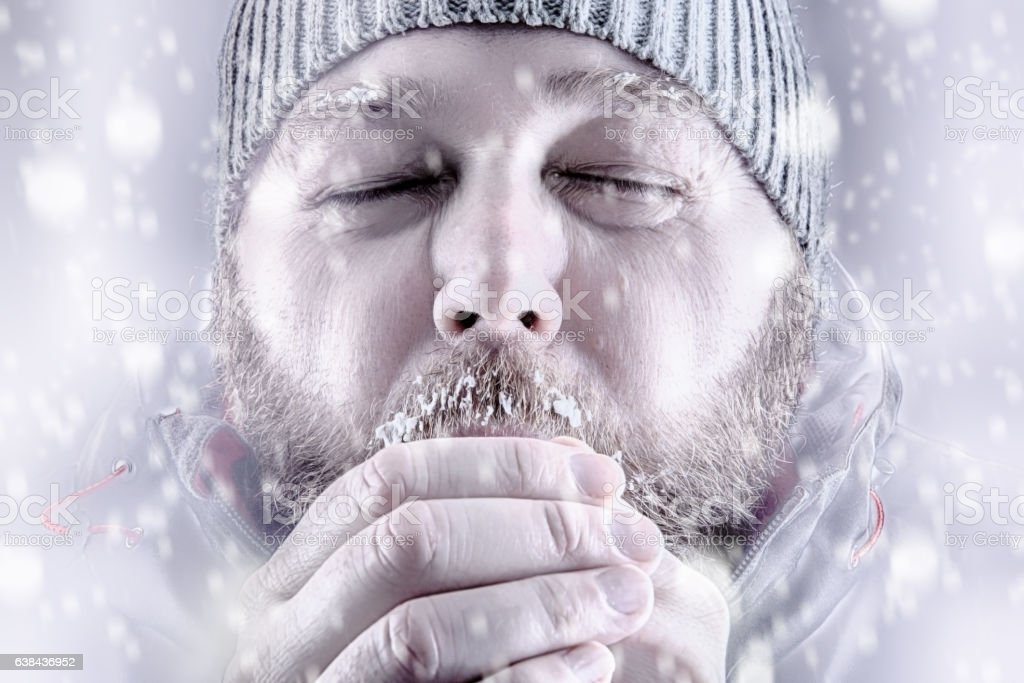 Man freezing in snow storm white out close up stock photo