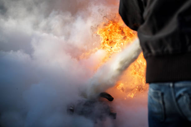 man from behind is fighting a fire with foam from a fire extinguisher, copy space in the smoke man from behind is fighting a fire with foam from a fire extinguisher, copy space in the smoke extinguishing stock pictures, royalty-free photos & images