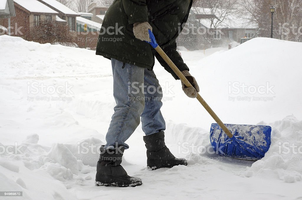Man from the neck down shoveling snow in a storm stock photo