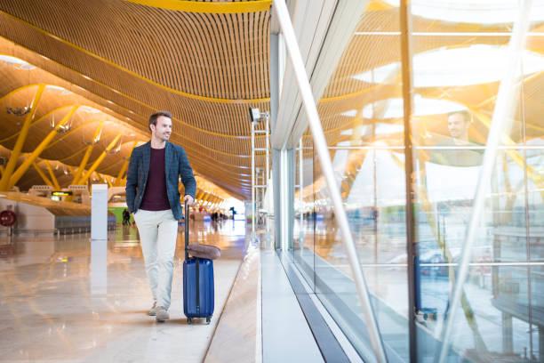 voorkant van de man lopen op de luchthaven gebruik mobiele telefoon - airport pickup stockfoto's en -beelden