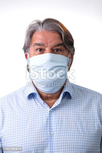 Man portrait with protection mask due to the world pandemic crisis. He is looking to the camera.