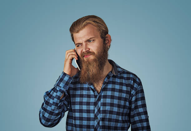 man frustrated by someone listening on his mobile phone - disconcert stock pictures, royalty-free photos & images