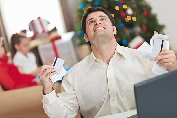 uomo frustrato con la sua famiglia natale bollette e di debito - holiday and invoice family foto e immagini stock