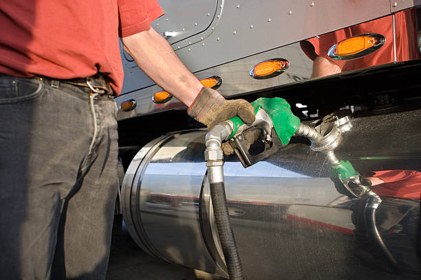 A man fueling a gas tank of a truck stock photo