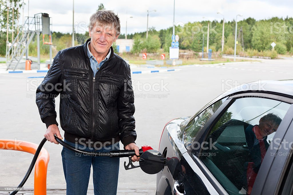 Man fueling modern car with petroleum in gas stations royalty-free stock photo