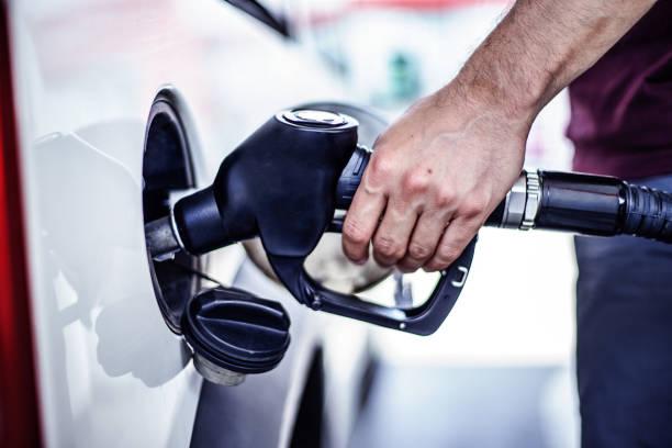 man fulling tank with fuel at bokeh background - riempire foto e immagini stock