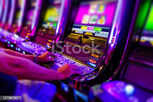 Man gambling on electronic slot machine in casino. Property released.