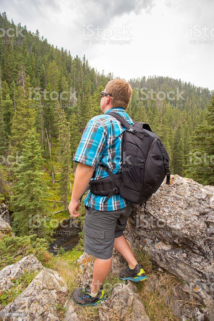 Man gazing from the top of a cliff. stock photo