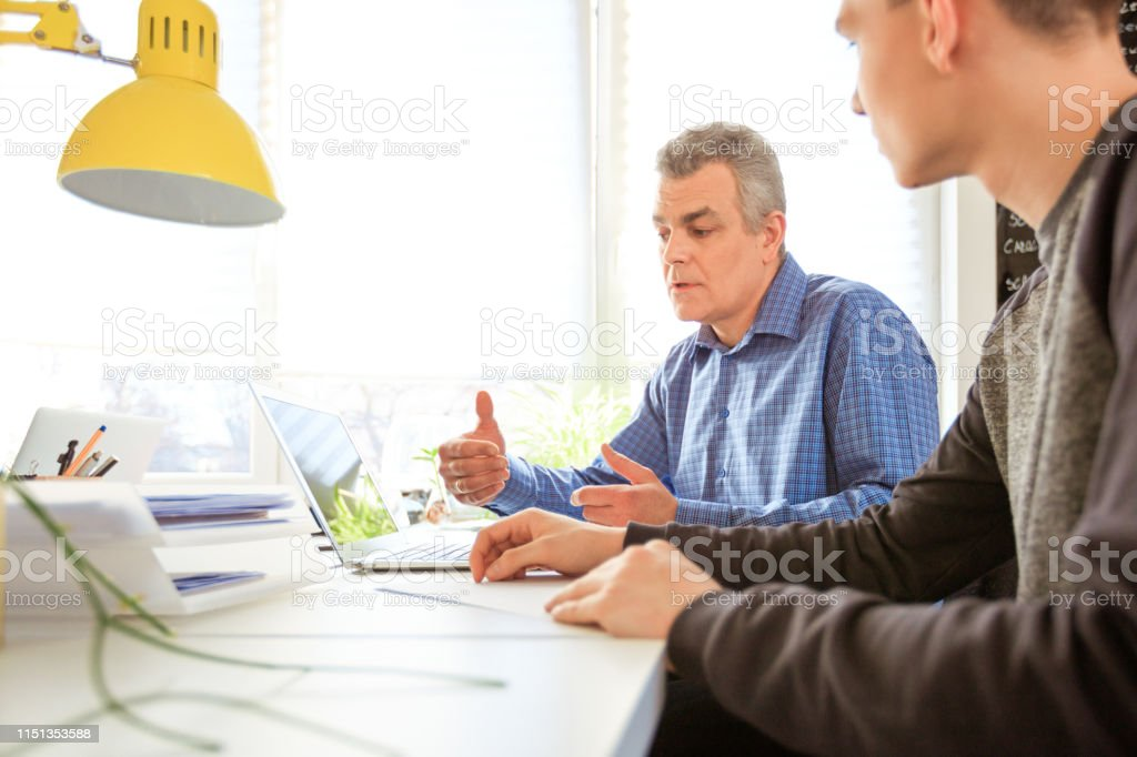 Man gesturing while guiding depressed student Mature man gesturing while guiding depressed student. Social worker is using laptop while having meeting with male at desk. They are sitting in university. 18-19 Years Stock Photo
