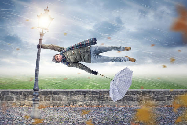 man gets blown away by a storm - weather stock photos and pictures