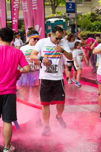 Man gets coated in pink paint, The Color Run Seattle Seattle, Washington, USA - May 10, 2015:  A man dashing through the Pink Zone paint area gets splattered with bright pink paint, as a participant in The Color Run 5k event. sopaatervinning stock pictures, royalty-free photos & images